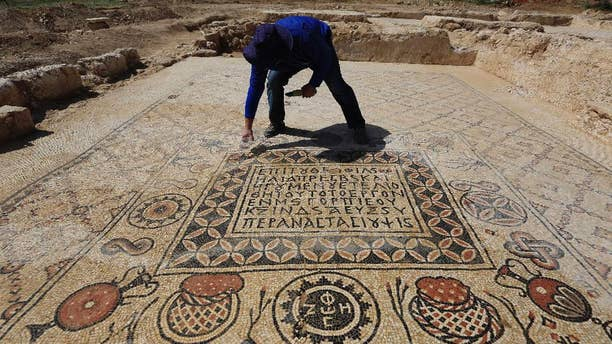 An Israeli Antiquities Authority archeologist Daniel Varge works on a Byzantine period monastery mosaic near a  village of Hura, Tuesday, April 1, 2014. Israel's Antiquities Authority has unveiled a monastery dating back about 1,400 years in the south of the country with an impressive mosaic floors that shed light on life in the region during the Byzantine period. (AP Photo/Tsafrir Abayov)
