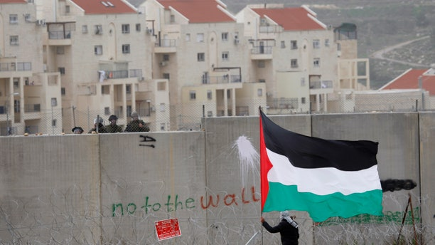 Feb. 17, 2012:  In this file photo, the West Bank Jewish settlement of Modiin Illit is seen in the background while a protestor waves a Palestinian flag in front of Israeli troops during a protest against Israel's separation barrier in the West Bank village of Bilin.