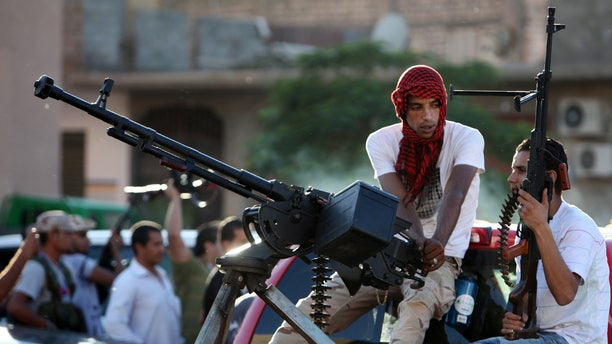 Revolutionary fighters sit on a truck mounted with a machine gun in the Abu Salim neighborhood of Tripoli, Libya, Friday, Oct. 14, 2011.
