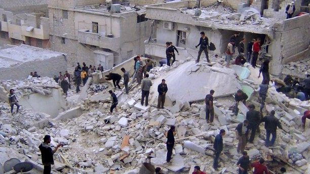 March 20, 2013: In this citizen journalism image provided by Aleppo Media Center AMC which has been authenticated based on its contents and other AP reporting, Syrian citizens search for dead bodies on the rubble of damaged buildings that were attacked by Syrian forces airstrikes, at al-Zarazir neighborhood, in Aleppo, Syria.