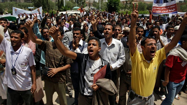 Students shout slogans as they protest on the Sanaa University campus to show their support for a boycott of university studies as part of protests demanding the resignation of Yemeni President Ali Abdullah Saleh, in Sanaa,Yemen, Sunday, Sept. 18, 2011.