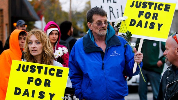 "October 22, 2013: Shana Curry, left, and her husband Scott Curry hold signs at the ""Justice for Daisy"" rally in Maryville, Mo. The rally was organized on the Internet on behalf of Daisy Coleman, a girl who says she was sexually assaulted nearly two years ago when she was 14. (AP Photo/The St. Joseph News-Press, Sait Serkan Gurbuz)"