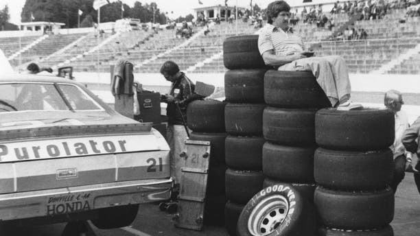 "MARTINSVILLE, VA — 1980: Driver Neil Bonnett uses a stack of Goodyear tires as a makeshift ""easy chair"" as he watches practice for a NASCAR Cup race at Martinsville Speedway. (Photo by ISC Images & Archives via Getty Images)"