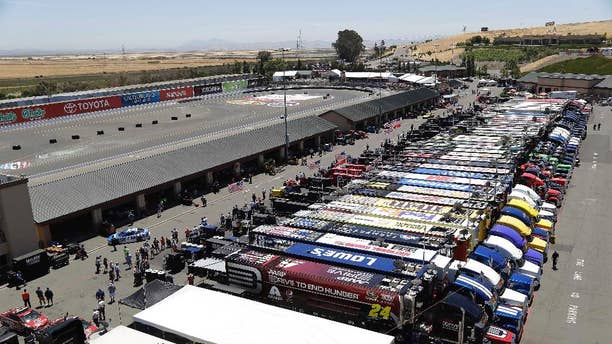 Jeff Gordon, left, pulls his car into the garage during practice for the NASCAR Sprint Cup Series auto race Friday, June 20, 2014, in Sonoma, Calif. (AP Photo/Eric Risberg)