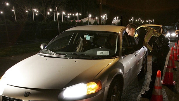 SAN BRUNO, CA - NOVEMBER 27:  San Bruno police officers stop cars at a DUI checkpoint on November 27, 2006 in San Bruno, California. San Francisco Bay Area law enforcement agencies have begun to set up DUI checkpoints as the holiday season gets underway.  (Photo by Justin Sullivan/Getty Images)