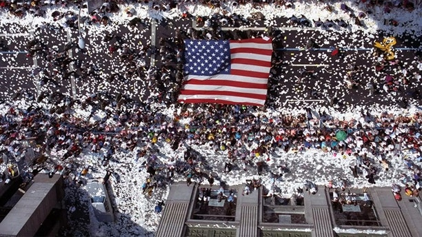 Marchers carry a giant American flag up Broadway in New York City on June 10, 1991 as part of a welcome home parade for veterans of Operation Desert Storm.
