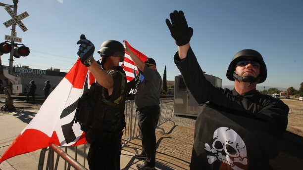 OCT. 24: File-Members of the white supremacist group, the National Socialist Movement, hold swastika flags and salute at the NSMÃs anti-illegal immigration rally near a Home Depot store in Riverside, California.   (Photo by David McNew/Getty Images)