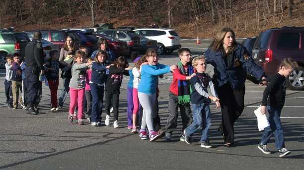 In this photo provided by the Newtown Bee, Connecticut State Police lead a line of children from the Sandy Hook Elementary School in Newtown, Conn. on Friday, Dec. 14, 2012 after a shooting at the school. (AP Photo/Newtown Bee, Shannon Hicks, File)