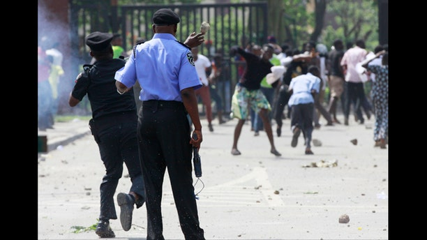 June 1, 2012: A policeman returns a thrown stone as youths run after policemen fired teargas on protesting students of university of Lagos, following the renaming of their school in Lagos, Nigeria.