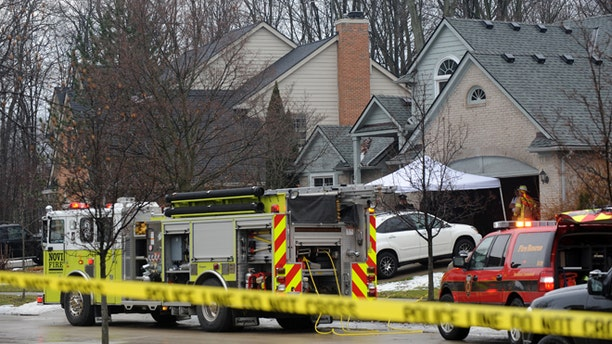 Police and fire officials investigate a house fire that killed five people at a home in Novi, Mich., Sunday, Jan. 31, 2016. Authorities say five restaurant workers were killed in the house fire near Detroit. The cause of the blaze is under investigation.  (Brandy Baker/Detroit News via AP)
