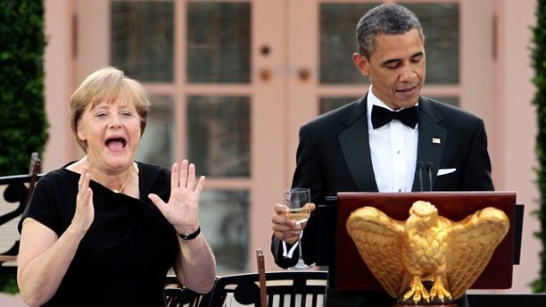 June 7: German Chancellor Angela Merkel, left, reacts as President Obama remembers to share a toast in her honor at a State Dinner in the Rose Garden of the White House in Washington.