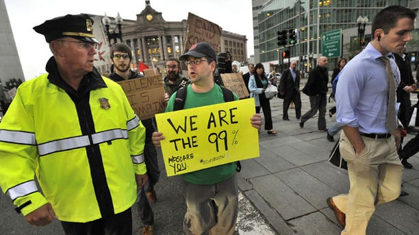 October 3: A marcher speaks with a police officer as they cross a street alongside morning commuters as the marchers set out from the Occupy Boston encampment in Dewey Square in front of the Federal Reserve building, in Boston.