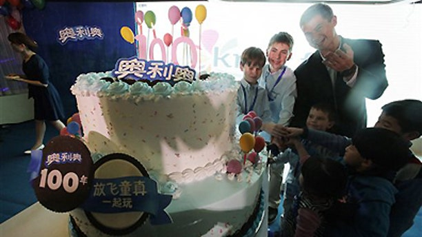Tuesday March 6, 2012: Shawn Warren, president of Kraft Foods China, back row right, and children cut the birthday cake for Oreo cookie's 100th anniversary celebration in Shanghai, China.