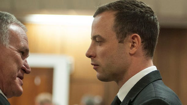 June 30, 2014: Oscar Pistorius listens to his lawyer Barry Roux, left, in court in Pretoria, South Africa.