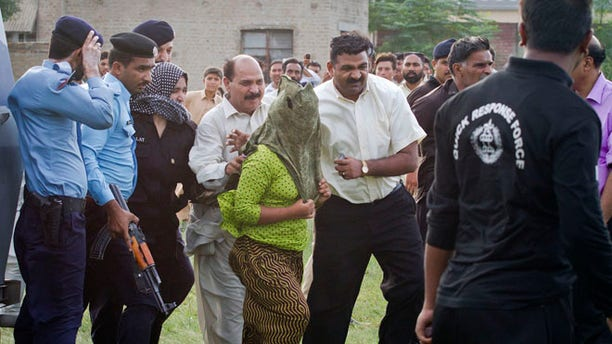 Sept. 8: Pakistani police officials escort a young Christian girl, center, accused of blasphemy for allegedly burning pages of a Quran, toward a helicopter following her release from central prison on the outskirts of Rawalpindi, Pakistan.