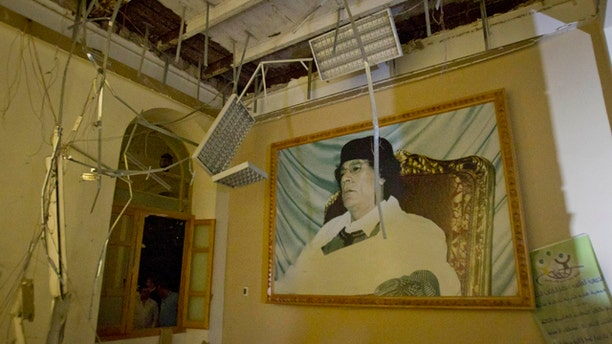 April 30: In this photo made on a government organized tour, a portrait of Moammar Gadhafi is seen inside damaged official building following an airstrike in Tripoli, Libya.