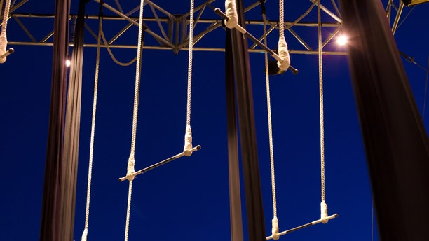 Empty standing trapezes against dark blue sky at twilight