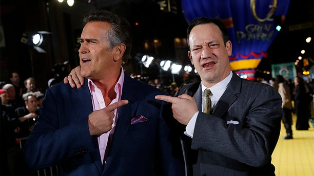 """(L-R) Actors Bruce Campbell and Ted Raimi share a light moment at the premiere of the Disney movie """"Oz the Great and Powerful"""" at the El Capitan Theatre in Hollywood, California February 13, 2013."""