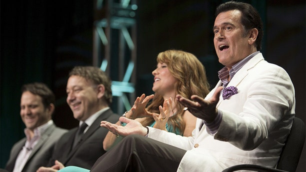 """Actor Bruce Campbell speaks, joined by showrunner Craig DiGregorio (L), director/executive producer Sam Raimi and actress Lucy Lawless, during the Starz """"Ash vs Evil Dead"""" panel at the Television Critics Association (TCA) Summer 2015 Press Tour in Beverly Hills, California July 31, 2015."""