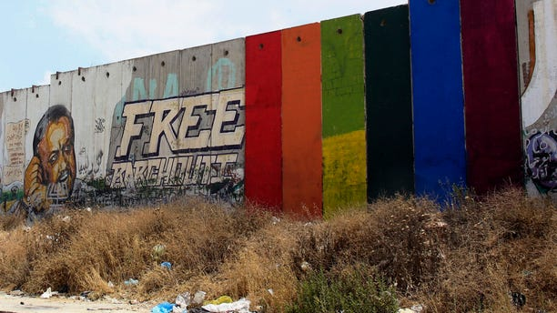 Monday, June 29, 2015: Palestinian artist Khaled Jarrar shows his painting of a rainbow flag on six slabs of the West Bank separation barrier in the West Bank city of Ramallah.