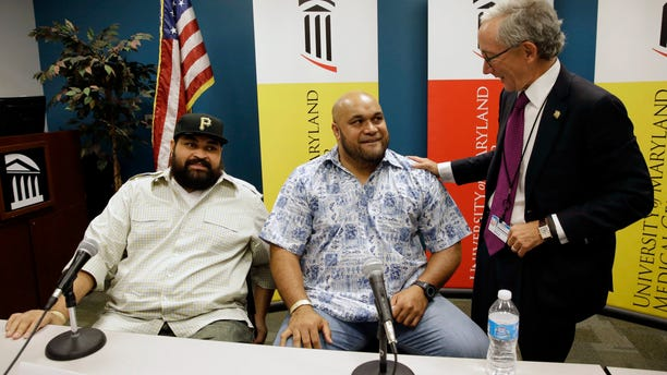 Sept. 17, 2014: Chris Kemoeatu, left, and his brother Ma'ake chat with Dr.  Matthew Weir after a news conference at the University of Maryland Medical Center in Baltimore.