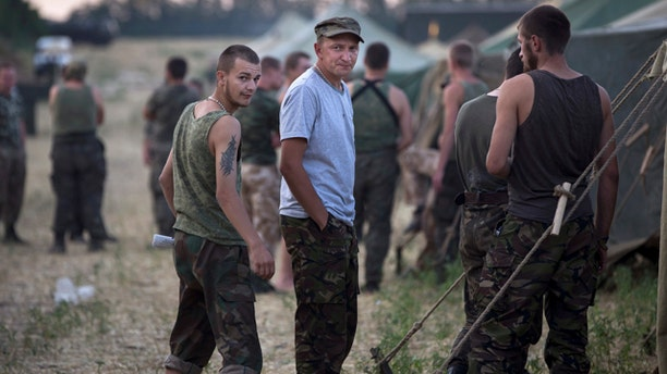 August 4, 2014: Ukrainian soldiers, who fled the conflict territory, spend their time at a tent camp near the Russia-Ukraine border just outside the village of Gukovo, Rostov-on-Don region, southern Russia. (AP Photo/Alexander Zemlianichenko)