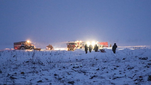 In this photo provided by the Russian Emergency Situations Ministry, Russian Ministry for Emergency Situations employees work at the scene of a AN-148 plane crash in Stepanovskoye village, about 25 miles from the Domodedovo airport, Russia, Sunday, Feb. 11, 2018.