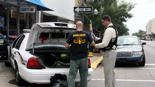 May 17: A bomb squad office and a hostage negotiator return a weapon to the trunk of the patrol car after a search for a gunman who was barricaded inside the landmark Pink House restaurant in Savannah, Ga.