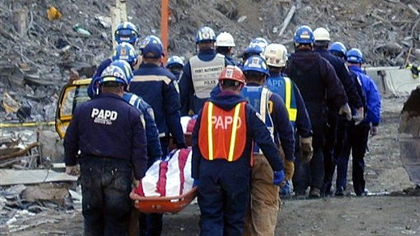 In this undated photo provided by Stony Brook University, New York City police and firefighters remove the body of a victim during recovery efforts at the World Trade Center in New York in the aftermath of the Sept. 11, 2011 attacks on the trade center.