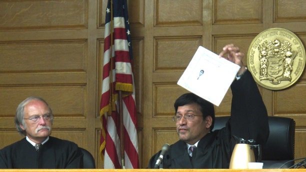 July 26: Sohail Mohammed holds up a copy of his citizenship papers at his ceremonial swearing in ceremony as a New Jersey Superior Court judge in Paterson, N.J. Mohammed gained the respect of many top law enforcement officials for his efforts to build bridges between the Muslim community and law enforcement in the aftermath of September 11th.