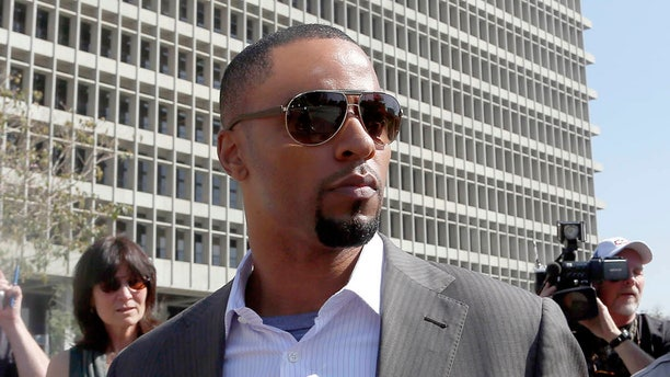 Feb. 14, 2014: Former NFL safety Darren Sharper leaves a courthouse in Los Angeles. An arrest warrant has been issued for Sharper and another man, accusing them of raping two women in New Orleans last year. Sharper also is under investigation in sexual assault cases in Florida, Nevada and Arizona and has pleaded not guilty to rape charges in Los Angeles. (AP/Nick Ut )