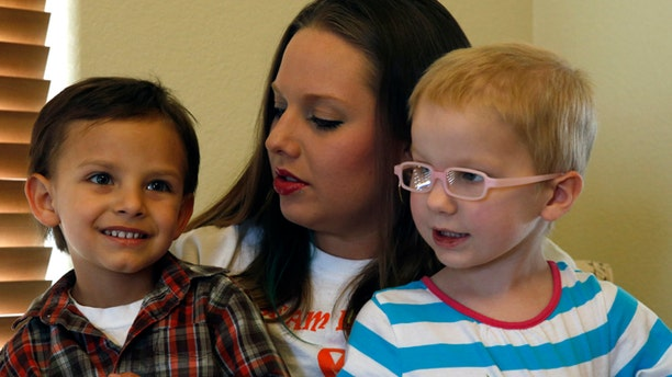 In this April 29, 2014 photo, mother of a child with cancer Sierra Riddle plays with her son Landon, age 4, left, and Landon's friend Dahlia, age 3, who also has cancer, during a play date at Dahlia's home in Colorado Springs. Landon and Dahlia's parents, frustrated with mainstream medical treatments and facing the possibility of intervention by child protective authorities, moved to Colorado to treat their children using what some describe as cutting edge cannabis medication. Hundreds of parents in similar situations find themselves at the center of a debate about how far government can and should reach when parents push against legal boundaries to save their childrens' lives.
