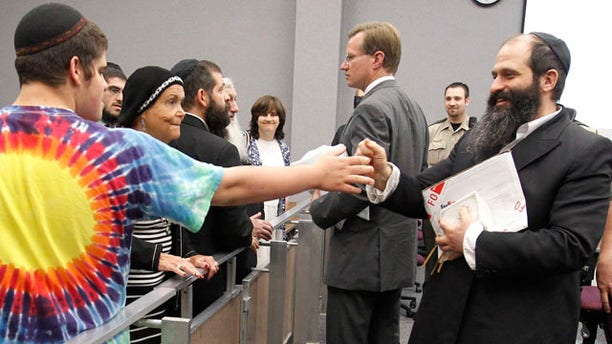 June 1: Moishe Rubashkin, 16, says hello to his father defendant Sholom Rubashkin, former Agriprocessors co-vice president, after his child labor trial ending early for lunch at the Black Hawk County Courthouse in Waterloo, Iowa. (AP)