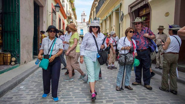 In this Wednesday, April 20, 2016, photo, smarTours tour director Pamela Boudrot, center, and local tour guide Enedis Tamayo, left, lead a group of tourists in Havana. The thaw in U.S.-Cuba relations has many small and medium-sized companies thinking about doing business with the nation that has largely been off-limits for more than half a century. Greg Geronemus, owner of smarTours, based in New York, began planning to increase his Cuba business two years ago, when he ran 15 tours. He expects to run 45 tours to Cuba this year, most of them leaving from Miami. (AP Photo/Desmond Boylan)