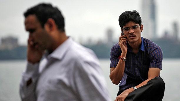 File photo - men speak on their mobile phones on a seafront in Mumbai Aug. 28, 2014.