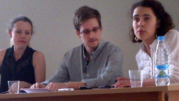 July 12, 2013: In this image provided by Human Rights Watch, NSA leaker Edward Snowden, center, attends a news conference at Moscow's Sheremetyevo Airport with Sarah Harrison of WikiLeaks, left.
