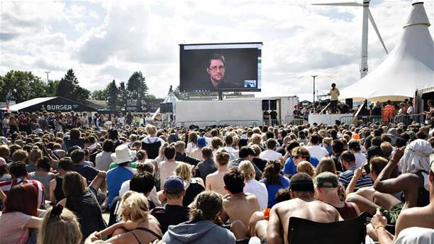 """Whistleblower Edward Snowden of the US, speaks to the crowd on a gigant screen at the Roskilde Festival in Roskilde, Denmark, Tuesday, June 28. 2016. """"You are being watched all the time and you have no privacy"""", Snowden said via a video link from his exile in Russia."""