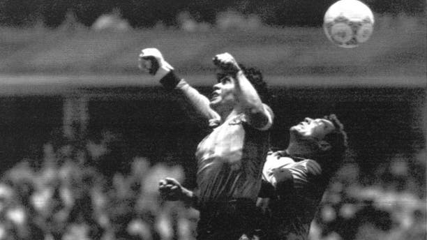 FILE - This is a Sunday, June 22, 1986 file photo of Argentina's Diego Maradona, left, as he is seen in the controversial action in which he knocked the ball with his left hand into the net of England's goalie Peter Shilton to score his team's first goal when Argentina defeated England 2-1 in the World Cup quarterfinal in the Mexico City Aztec stadium. Cheating. It's an ugly side of the beautiful game and it involves just about every aspect of it. The World Cup in Brazil begins in June and the founders of association football would shudder at how entrenched deception and trickery have become in the modern game. (AP Photo/El Grafico, File)
