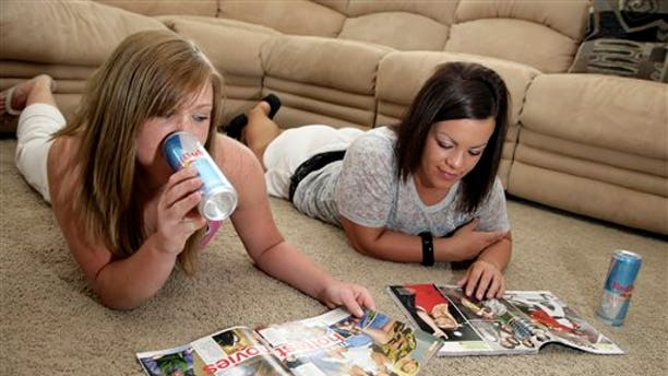 FILE - In this June 3, 2008 file photo, Megan Ward, left, drinks an energy drink with her friend Mykel Prescott from Parker, Colo., at Ward's home in Castle Rock, Colo. The journal Pediatrics published online Monday, Feb. 10, 2014, results of research into trends in the caffeine intake among children and young adults. (AP Photo/Jack Dempsey, File)