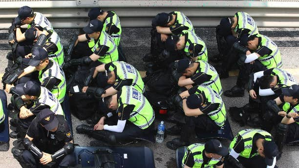 Police officers take a rest near Evangelical Baptist Church in Anseong, South Korea, Wednesday, June 11, 2014. Thousands of South Korean police officers stormed a church compound Wednesday in their hunt for a fugitive billionaire businessman over April's ferry sinking that left more than 300 people dead or missing, officials said. (AP Photo/Ahn Young-joon)