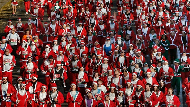 "Revelers dressed as Santa Claus run during a ""mini-marathon"" in Madrid, Spain, Saturday, Dec. 14, 2013. Around 6,000 people dressed as Santa Claus and his elves have run a âmini-marathonâ through the streets of Madrid to promote festive cheer as the country tries to emerge from a two-year recession. While grown-ups dressed in red costumes with wispy white beards, children donned green elf outfits to run the 5.5 kilometer (3.4 miles) course through the city center. The race was organized Saturday by one of Spainâs leading department stores and it contributed 1 euro ($1.34) for each entrant to a charity that buys Christmas presents for deprived children around the world. (AP Photo/Andres Kudacki)"