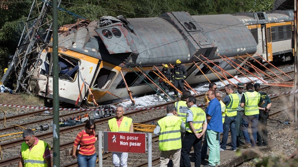 Emergency personnel attend the scene after a passenger train traveling from Vigo to Porto, in neighboring Portugal, derailed in O Porrino,  in Spain's northwestern Galicia region, killing  and injuring people, authorities said Friday Sept. 9, 2016. The train had three cars. The front one came completely off the track and hit a post next to the line, leaving it leaning to one side. The back two cars were partly off the tracks. Spanish media said the train was carrying around 60 passengers.(AP Photo/Lalo R. Villar)