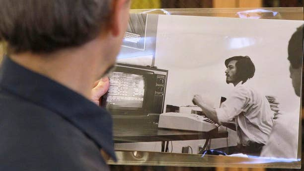 Oct. 25, 2011: Curator Henry Lowood looks at an old photograph of Steve Jobs at Stanford's Green Library in Stanford, Calif. Historians and entrepreneurs who want to understand the rise of Apple Inc. and its founder Steve Jobs will find a treasure trove of clues in the Silicon Valley Archives.
