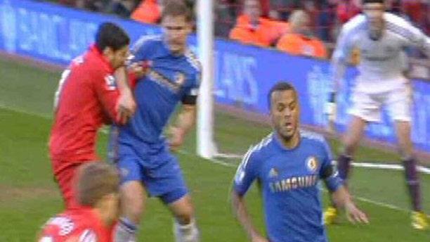Luis Suarez of Liverpool bites Branislav Ivanovic of Chelsea.