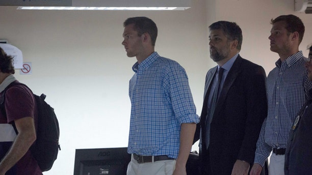 Accompanied by Brazilian lawyer Sergio Riera, second from right, American Olympic swimmers Gunnar Bentz, left, and Jack Conger, right, leave a police station in the Leblon neighborhood of Rio de Janeiro, Brazil, Thursday, Aug. 18, 2016. The two were taken off their flight from Brazil to the U.S. on Wednesday by local authorities amid an investigation into a reported robbery targeting Ryan Lochte and his teammates. A Brazilian police officer told The Associated Press that Lochte fabricated a story about being robbed at gunpoint in Rio de Janeiro. (AP Photo/Mauro Pimentel)