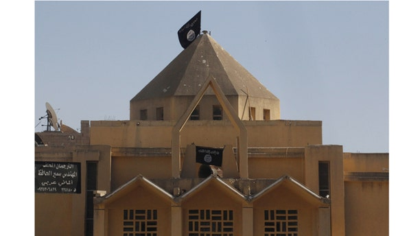 September 27, 2013: Flags of the Islamic State of Iraq and the Levant are hung on The Martyrs Church in  the city of Raqqa. The Al-Qaeda linked groups removed crosses from the structure and hoisted their flags.