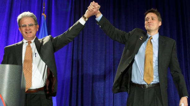 Nov. 2: Matt Pinnell, right, Oklahoma GOP chairman, lifts up the arm of U.S. Senator Tom Coburn, left, at a Republican watch party in Oklahoma City.