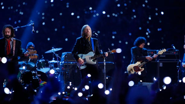 Tom Petty (C) and guitarist Mike Campbell (L) play with the band 'Tom Petty and the Heartbreakers' at halftime of the NFL's Super Bowl XLII football game between the New England Patriots and the New York Giants in Glendale, Arizona February 3, 2008.     REUTERS/Mike Blake (UNITED STATES)