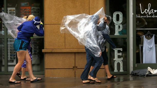Pedestrians brave the wind rushing down Atlantic Ave. in Virginia Beach, Va., on Saturday, Sept. 3, 2016, as Tropical Storm Hermine approaches the region. The National Hurricane Center says Tropical Storm Hermine could bring 4 to 7 inches of rain to southeastern Virginia and the Atlantic coastal portion of Maryland as well as 1 to 4 inches of rain over southern Delaware, southern and eastern New Jersey and Long Island through Monday morning.  (Stephen M. Katz/The Virginian-Pilot via AP)