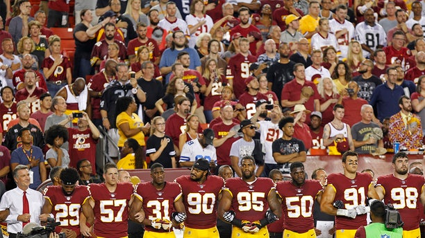 Sep 24, 2017; Landover, MD, USA; Washington Redskins president Bruce  Allen (L) stands with Redskins players arm in arm during the national anthem prior to their game against the Oakland Raiders at FedEx Field. Mandatory Credit: Geoff Burke-USA TODAY Sports - 10305314